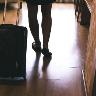 Young woman entering in a hotel room with her suitcase