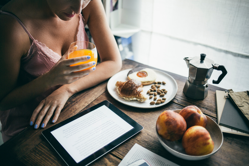 Caucasian woman reading an e-book on her tablet while having breakfast.